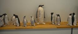 Ceramic figurines of penguins on wooden shelf