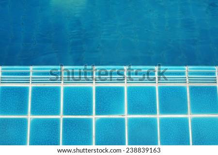 ceramic  floor beside the blue swimming pool, top view
