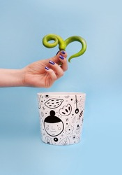 Ceramic flower pot with hand drawn doodle illustrations with a hand holding green peppers on it, front view planting and gardening concept on blue background