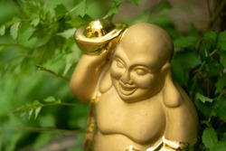 Ceramic gilded statue of the god of wealth and fun of Hotei in the garden. A broad smile gives a spring mood