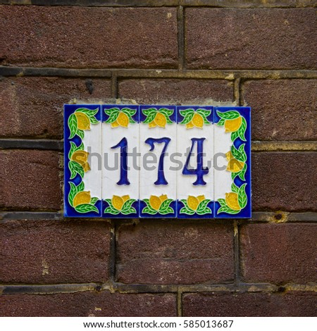 Ceramic house number one hundred and seventy four (174).
