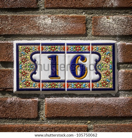 Ceramic house number sixteen surrounded by a decoration for Number 16 house