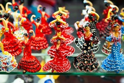 Ceramic mosaic and painted flamenco dancers figurines in colorful traditional dresses on showcase of Spanish souvenir shop..