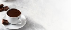Ceramic mug with hot chocolate and chocolate slices on concrete background. Large image for web banner.