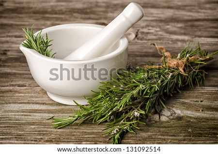 ceramic pestle and rosemary on wood