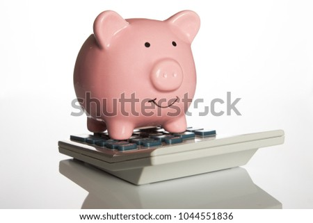 Ceramic pink piggy bank standing on a calculator in a financial, investment or savings concept isolated on white #1044551836