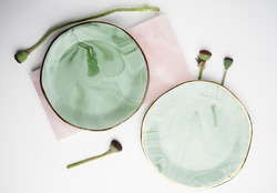 Ceramic plates with green stains and golden borders. Perfect handmade plates with the flower stalks around. Plates on the pink flat.