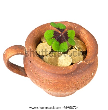 ceramic pot with money coins and clover leaf on white background - stock photo
