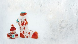 ceramic santa claus boot with toys stands on the snow. A toy Santa in a boot and a snowman next to it. copy space
