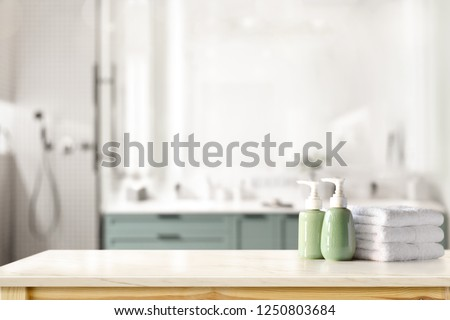 Ceramic shampoo, soap bottle and towels on counter over bathroom background. table top and copy space