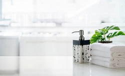 Ceramic shampoo, soap bottle and towels on counter over kitchen room background. White top table and copy space.