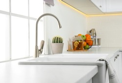 Ceramic sink and modern tap in stylish kitchen interior