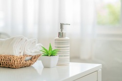 Ceramic soap, shampoo bottles and white cotton towels with green plant on white counter table inside a bright bathroom background