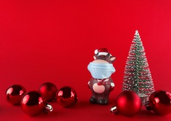 Ceramic statuette of Ox in medical mask, Christmas tree and balls on red backgroud with copy space. Symbol of New Year 2021.
