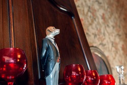 Ceramic statuette, sculpture of a gentleman's white dog. The figure of a dog stands among red glass glasses in the interior