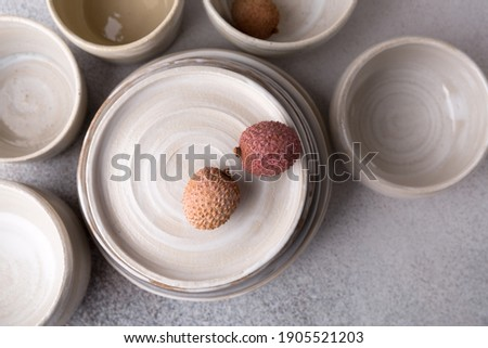Ceramic tableware. Close-up. Empty craft ceramic plates, bowls and cups on light background. Сток-фото ©