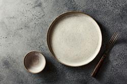 CERAMIC TABLEWARE. Flat ceramic plate and fork. Top view.