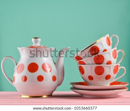 Ceramic teapot, a stack of cups in polka dots on a wooden table isolated on a blue pastel background. Copy space\n