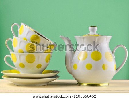 Ceramic teapot, a stack of cups in polka dots on a wooden table isolated on a blue pastel background. Copy space\r