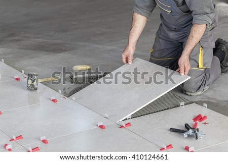 Ceramic Tiles. Tiler placing ceramic wall tile in position over adhesive with lash tile leveling system #410124661