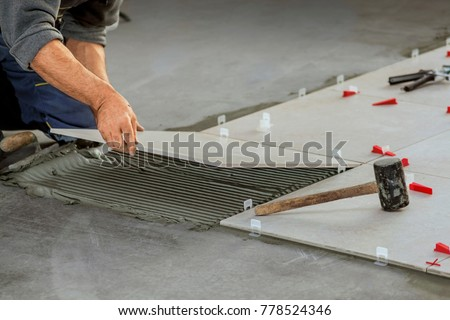 Ceramic Tiles. Tiler placing ceramic wall tile in position over adhesive with lash tile leveling system #778524346