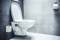 Ceramic white toilet bowl near grey wall, side light in the modern bathroom