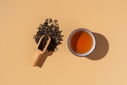 Ceramics bowl with black puer tea ,dry pu-erh tea leaves in a wooden bamboo plate on a beige background,minimalism style,hard light