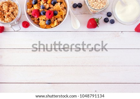Cereal and ingredients for a healthy breakfast forming a top border over a white wood background. Top view. Copy space.