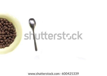 Cereal chocolate balls with yellow bowl on white background .