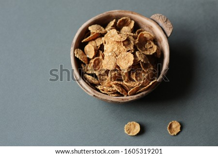 cereal flakes in a ceramic bowl on a grey paper background with a blank space for inscriptions. Concept of healthy eating, healthy eating
