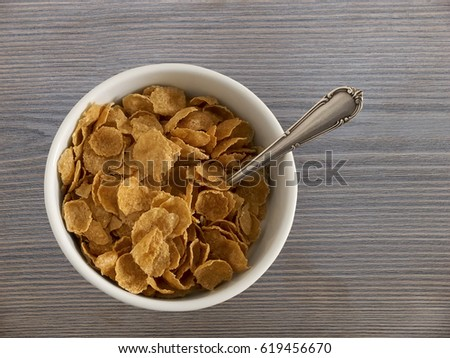 Cereal flakes in bowl and silver spoon on wooden board. Top view.