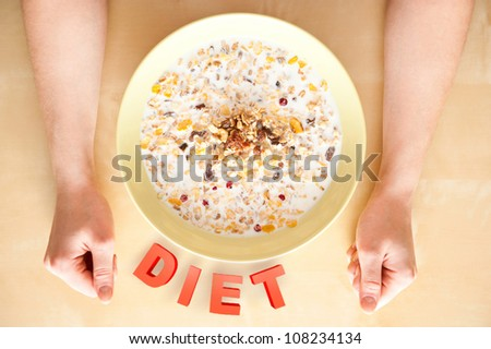 Cereal muesli breakfast with dried fruit and nuts and milk and woman hands on table. Top View. Diet food concept