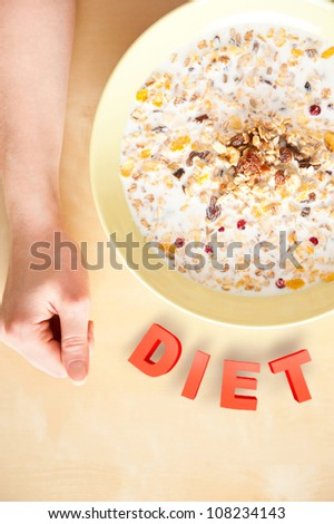 Cereal muesli breakfast with dried fruit and nuts and milk and woman hands on table. Top View. Diet food concept - stock photo