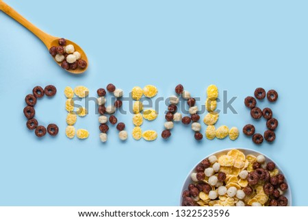 Cereals bowl and spoon on a blue background. Glazed, chocolate balls, rings and corn flakes for healthy dry breakfast. Cereals concept  #1322523596