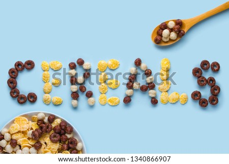 Cereals bowl and spoon on a blue background. Glazed, chocolate balls, rings and corn flakes for healthy dry breakfast. Cereals concept  #1340866907