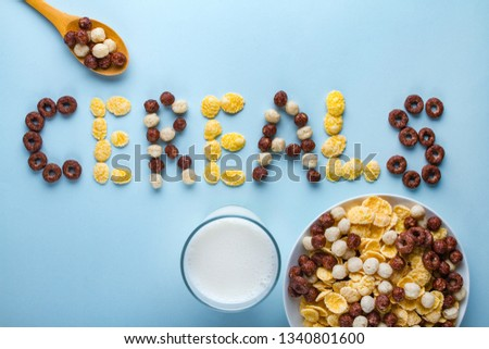 Cereals bowl, spoon and a glass of milk on a blue background. Glazed, chocolate balls, rings and corn flakes for healthy dry breakfast. Cereals concept  #1340801600