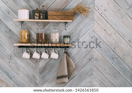 Cereals in glass jars on shelf, white cups, towel hang on hooks on kitchen  wooden wall. Cookware concept, kitchenware Photo stock ©