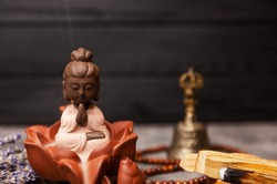 Ceremony of worship of the Buddha. Incense sticks. Spa and aromatherapy. Buddha figure on grey board with an aroma smoke from burning incense sticks flutters on the background. Herbal medicine