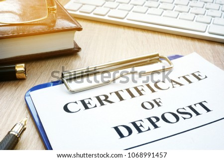 Certificate of deposit and pen on a desk.