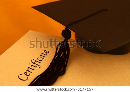 certificate printed on a yellowish grainy textured paper and a black graduation cap, on yellow - orange background