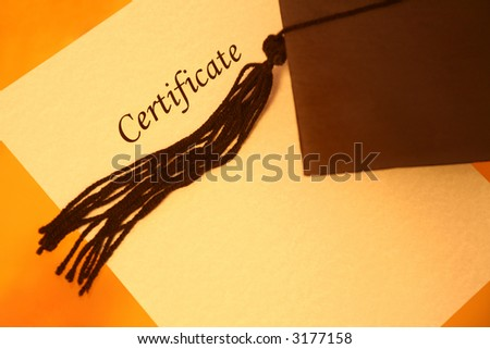 certificate printed on a yellowish grainy textured paper and a black graduation cap on yellow-orange background, top view