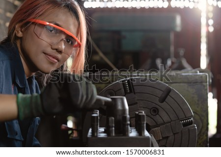 Certified industry female mechanical engineer working on industrial factory machinery - Skilled apprentice technician woman wearing safety equipment - Training, repair and diversity at work concept Foto stock ©