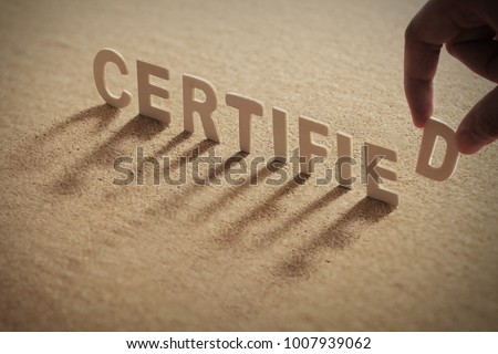 CERTIFIED wood word on compressed or corkboard with human's finger at D letter.