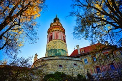 Cesky Krumlov Castle Tower, Cesky Krumlov, Czech Republic In autumn, the yellow of the leaves contrasts with the blue of the sky