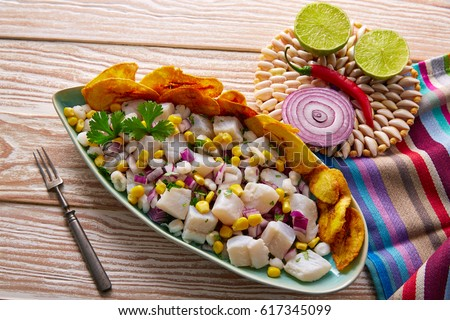 Ceviche peruvian recipe with fried banana and ingredients on wooden table