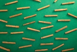 Ceylon cinnamon tree sticks scattered on green background, top view
