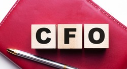 CFO is made up of wooden cubes that stand on a burgundy notebook near the pen. Business concept