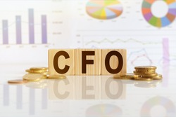 CFO the word on wooden cubes, cubes stand on a reflective surface, in the background is a business diagram. Business and finance concept
