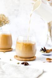 Chai Latte pouring shot. Chai Latte Drink. Pouring oat milk into chai latte glass.