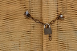Chain and lock on a door covered with net